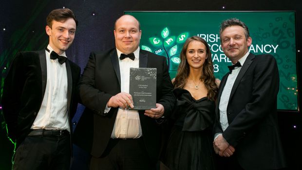 Carl Churchill, Managing Director, NetPay Solutions Group presents the CSR Initiative of the Year Award to Sadbh McCarrick, John Mc Carrick and Conn Mc Carrick, John McCarrick & Associate