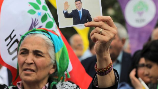 A supporter of Turkey's main pro-Kurdish Peoples' Democratic Party (HDP) with a picture of its jailed former leader and presidential candidate Selahattin Demirtas, in Istanbul. Photograph: Huseyin Aldemir