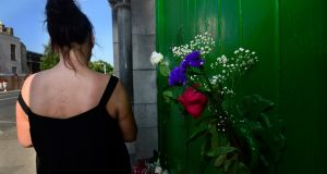 A former resident outside the laundry at Sean McDermott Street, where there are  posies and a bouquet left at the door in memory of women who spent their lives inside. Photograph: Cyril Byrne / The Irish Times