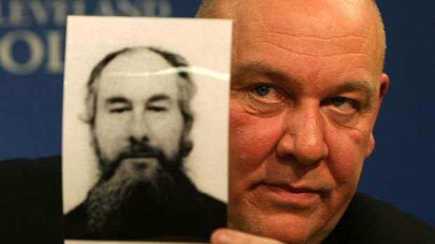 Detective Superintendent Tony Hutchinson holds the fake passport picture of John Darwin, the canoeist who turned up after being presumed dead in 2002. Photograph: Christopher Furlong/Getty Images