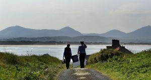 Presiding Officer Carmel McBride and Garda Alan Gallagher carry the polling box for the abortion referendum on Inishbofin. Photograph: Photograph: Reuters