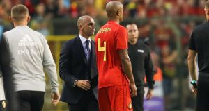 Belgium boss Roberto Martinez speaks to Vincent Kompany as the defender leaves the pitch with a groin injury. Photograph: Bruno Fahy/AFP