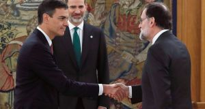 Spain's new prime minister, Pedro Sánchez, left, shakes hands with outgoing premier Mariano Rajoy,  next to Spain's King Felipe VI. Photograph: AFP Photo