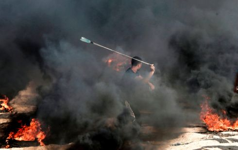 A Palestinian fires a stone towards Israeli forces at the border with the Gaza strip. Photograph: Mahmud Hams/AFP/Getty Images