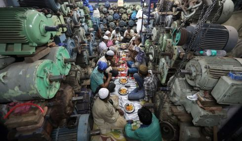 Indian Muslims gather for the Iftar (breaking fast) meal inside a water pump shop in the old quater of Delhi. Photograph: Rajat Gupta/EPA