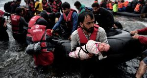A migrant carrying his baby as they come ashore along with other refugees and migrants arriving on the Greek island of Lesbos after crossing the Aegean Sea from Turkey. Photograph: Aris Messinis/AFP/Getty Images