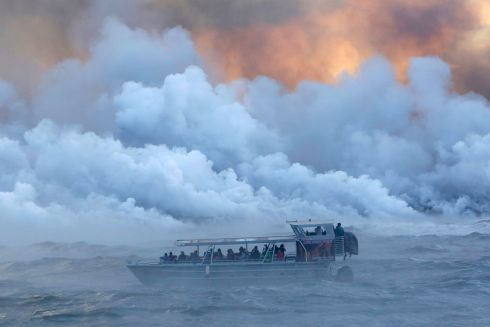 VOLCANIC RAGE: People watch from a tour boat as lava flows into the Pacific Ocean in the Kapoho area, east of Pahoa, during ongoing eruptions of the Kilauea Volcano in Hawaii, US. Photograph: Terray Sylvester/Reuters