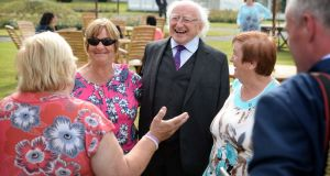 Twin sisters Mairead Manley (left) and Breda Kennedy, survivors of the Goldenbridge Magdalene laundry stand with president Michael D Higgins as Roseanna Murphy speaks. Photograph: Dara Mac Dónaill