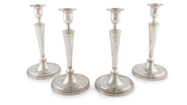 Four silver candlesticks.