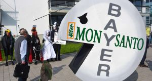 A protester in  a pill-shaped costume demonstrates against Bayer's takeover of Monsanto by German chemicals firm Bayer outside the World Conference Centre  in Bonn. Photograph: Patrik Stollarz/AFP/Getty Images
