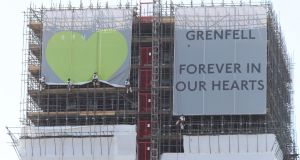 Banners are unveiled on the outside of Grenfell Tower in west London on Wednesday. Photograph: Yui Mok/PA Wire