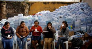 Women drink coffee at a collection centre at an area affected by the eruption of the  Fuego volcano in Alotenango, Guatemala, on Thursday. Photograph: Jose Cabezas/Reuters