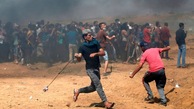 Palestinian protesters use slingshot to throw rocks at Israeli forces. Photograph: Mohammed Abed/AFP/Getty Images