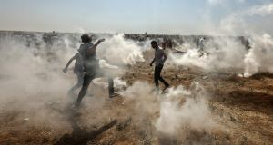Palestinian protesters take cover from tear gas shot by Israeli forces. Photograph: Mahmud Hams/AFP/Getty Images