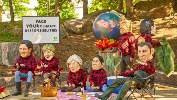 Oxfam activists imitate the leaders of the G7 nations as they protest against the warming global responsibility during the G7 Summit in Quebec City. Photograph: Andre Pichette/EPA