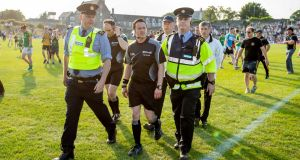 Referee Paddy Neilan is escorted off the field at the full time whistle. Photograph: Morgan Treacy/Inpho