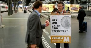 A member of the sovereign money initiative, a referendum campaign that would abolish traditional bank lending and allow only money created by the Swiss National Bank (SNB), campaigns for a Yes vote. Photograph: Arnd Wiegmann/Retuters