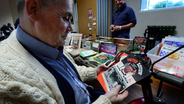 Richard Salenger looks through some Manchester United programmes from the 1950s. Photograph: Cyril Byrne