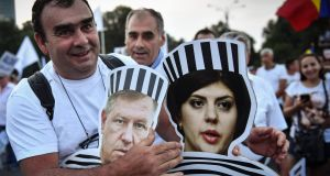 Pro-government supporter holds cutouts of Romanian president Klaus Iohannis and head of anti-corruption agency Laura Codruta Kovesi dressed as prisoners at a meeting organised by the PSD  ruling party in Bucharest. Photograph: Daniel Mihailescu/AFP/Getty