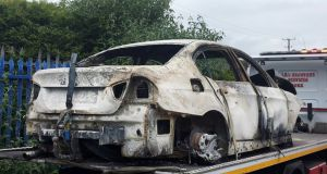 The burned-out car from which gardaí recovered a firearm in Waterfall, Co Cork. Photograph: Daragh McSweeney/Provision