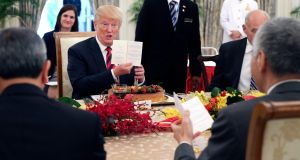 US president Donald Trump  holds up a menu card during a working lunch with Singapore's prime minister Lee Hsien-loong at the Istana. Photograph: Singapore ministry of communication/EPA