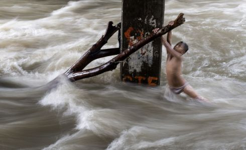 PLAYING FOR REAL: A boy holds on to a partially submerged tree trunk as he plays under a bridge in a swollen river in Manila, the Philippines. The rise in water levels was caused by heavy rains. Photograph: Noel Celis/AFP/Getty Images