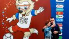 People take a picture front of a banner Zabivaka, the official mascot for the 2018 FIFA World Cup, in Saransk. Photograph:Juan Barreto/Getty Images