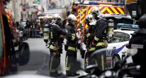 French police and firemen secure the area where a man has taken people hostage at a business in Paris, France. Photograph: Benoit Tessier/Reuters.