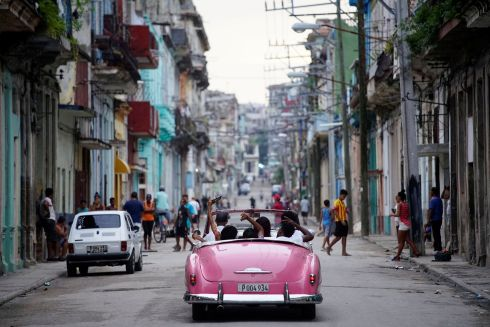 GOOD TIMES: Tourists live it up in a vintage car in Havana, Cuba, a location famed for its well-loved older automobiles. Photograph: Alexandre Meneghini/Reuters