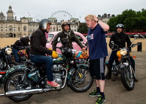 FANCY BIKES: British foreign secretary Boris Johnson stops while jogging through Horse Guards in London to talk to Simon de Burton (left) and Sam Pelly (centre), who are taking part in the Elephant Family charity's Concours d'elephant, a cavalcade of Royal Enfield motorbikes and Indian-inspired vehicles travelling around the city to raise awareness of the plight of Asia's endangered elephants. Photograph: Steven Paston/PA Wire
