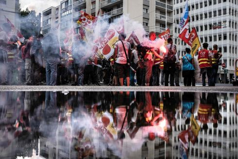 DOUBLE TROUBLE: French railway workers are reflected in a puddle as they demonstrate with banners, flags and flares in Lyon, on the 15th day of rolling train strikes against the planned overhaul of French national railway operator SNCF. Photograph: Jeff Pachoud/AFP/Getty Images