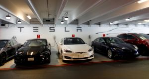 Tesla Model 3s and Xs are shown charging in an underground parking lot next to a Tesla store in San Diego, California. Photograph: Mike Blake/Reuters