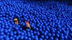 An attendee at the CeBIT tech fair in Hanover, Germany, buries himself in a ball pit at the IBM stand. Photograph: Kriztian Bocsi/Bloomberg