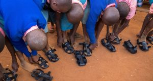 Children try on the shoe that grows, The sandals are made of a compressed rubber sole and tough synthetic leather straps at the top.