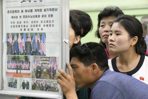CAPTIVE AUDIENCE: North Koreans watch the displayed local newspapers reporting the summit between the US and North Korea at a subway station in Pyongyang. Photograph: Kyodo news agency/via Reuters