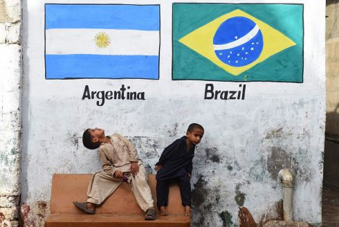 EXCITEMENT BUILDING: Children sit under Argentinian and Brazilian flags ahead of the Fifa World Cup, in the Lyari neighbourhood of Karachi, Pakistan. Photograph: Rizwan Tabassum/AFP/Getty Images