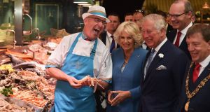 Prince Charles, Prince of Wales and Camilla, Duchess of Cornwall meet fishmonger Pat O'Connell as they visit the English Market. Photograph: Charles McQuillan/Getty Images.