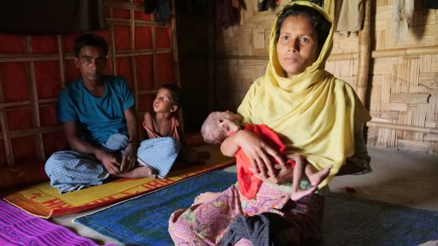 Rahima Khatun (30) holding her seven-month-old niece Taslima, whose mother died shortly after giving birth. In the background, her husband Muhammad Ali with one of their five other children, Sayedul Amin. Photograph: Kathleen Harris