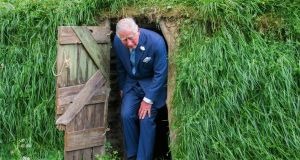 Prince  Charles exits a model of a famine bothán during his visit to UCC. Photograph: Daragh Mc Sweeney/Provision.