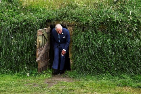 The Prince of Wales emerges from a recreation of a Famine-era mud hut on the campus of University College Cork. Photograph: Clodagh Kilcoyne/Reuters