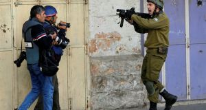 An Israeli soldier shouts and  aims his weapon at a videographer and photographer during clashes with Palestinian demonstrators at a protest last December against US  president Donald Trump's decision to recognise Jerusalem as the capital of Israel, in the West Bank city of Hebron. File photograph: Mussa Qawasma/Reuters