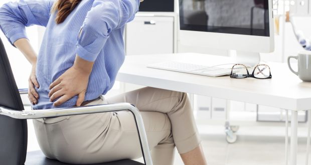 Crossing your legs while sitting at your desk creates asymmetry that causes hip problems. iStockphoto/Getty Images