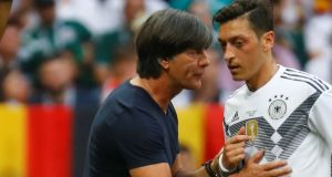 Germany coach Joachim Low speaks with Mesut Ozil after their Group F loss to Mexico at the 2018 World Cup. Photo: Kai Pfaffenbach/Reuters