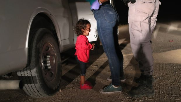 A two-year-old Honduran asylum seeker cries as her mother is searched and detained near the US-Mexico border on June 12th in McAllen, Texas. The asylum seekers had rafted across the Rio Grande from Mexico and were detained by US Border Patrol agents before being sent to a processing center for possible separation. Photograph: John Moore/Getty Images