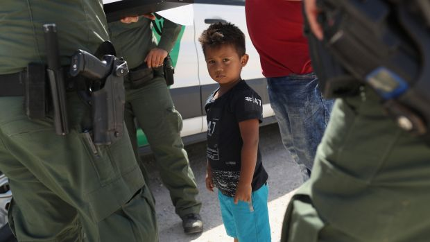 US border patrol agents take into custody a father and son from Honduras near the US-Mexico border on June 12th, near Mission, Texas. The asylum seekers were then sent to a US Customs and Border Protection (CBP) processing center for possible separation. Photograph: John Moore/Getty Images