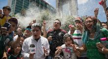 A reporter and fans are covered in foam during the celebration of Mexico's 2018 World Cup win over Germany at the Angel of Independence in Mexico City. Photo: Anthony Vazquez/AP Photo
