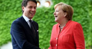 Prime Minister of Italy Giuseppe Conte shakes hands with German chancellor Angela Merkel: exploration of a bilateral refugee deal. Photograph: Clemens Bilan