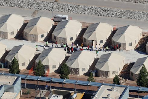 "Immigrant children, many of whom have been separated from their parents under a new ""zero tolerance"" policy by the Trump administration, are shown walking in single file between tents in their compound next to the Mexican border in Tornillo, Texas, U.S. June 18, 2018.        REUTERS/Mike Blake"