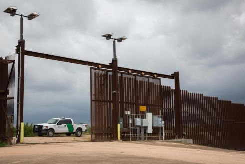 "A US Border Patrol agent keeps watch at a gate On the US-Mexico border fence on June 18, 2018 near San Benito, Texas. President Donald Trump vowed on June 18 that the United States would not become a ""migrant camp,"" as he faced soaring pressure to end the separation of immigrant families on America's southern border. / AFP PHOTO / Loren ELLIOTTLOREN ELLIOTT/AFP/Getty Images"