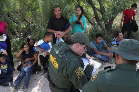 Central American asylum seekers wait as U.S. Border Patrol agents take groups of them into custody on June 12, 2018 near McAllen, Texas. The families were then sent to a U.S. Customs and Border Protection (CBP) processing center for possible separation. U.S. border authorities are executing the Trump administration's zero tolerance policy towards undocumented immigrants. U.S. Attorney General Jeff Sessions also said that domestic and gang violence in immigrants' country of origin would no longer qualify them for political-asylum status.  (Photo by John Moore/Getty Images)